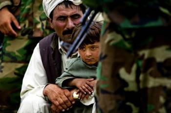 Father and child in Afghanistan near soldier